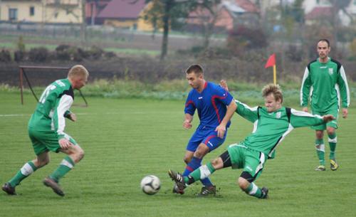 Łukasz Ziółkowski z Korony (w niebieskiej koszulce) w pojedynku z piłkarzami Nefrytu